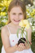Young girl outdoors holding flower smiling - stock photo