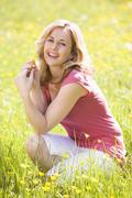 Woman outdoors holding flower smiling - stock photo