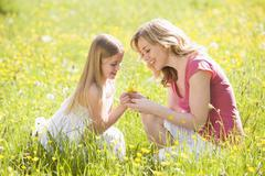 Mother and daughter outdoors holding flower smiling Stock Photos