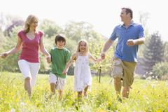 Family walking outdoors holding hands smiling - stock photo