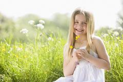 Young girl sitting outdoors holding flower smiling - stock photo