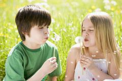 Two young children sitting outdoors blowing dandelion heads smiling - stock photo