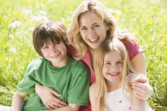 Mother and two young children sitting outdoors smiling Stock Photos