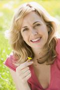 Woman sitting outdoors holding flower smiling - stock photo