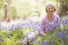 Stock Photo of Woman sitting outdoors with flowers smiling
