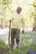 Man walking outdoors with walking stick smiling - stock photo