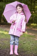 Young girl outdoors with umbrella smiling Stock Photos