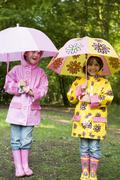 Two sisters outdoors in rain with umbrellas smiling Stock Photos