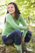Woman outdoors in woods sitting on log smiling - stock photo