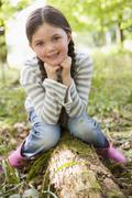 Young girl outdoors in woods sitting on log smiling - stock photo