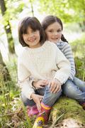 Two sisters outdoors in woods sitting on log smiling - stock photo