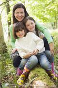 Mother and daughters outdoors in woods sitting on log smiling - stock photo