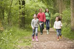 Family walking on path holding hands smiling Stock Photos