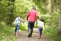 Father and daughters walking on path holding hands Stock Photos