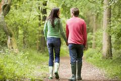Couple walking on path holding hands Stock Photos