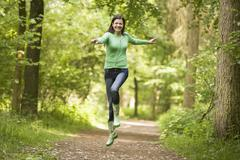 Woman jumping on path smiling Stock Photos