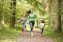 Mother and daughters skipping on path smiling Stock Photos