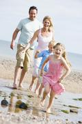 Family running at beach smiling Stock Photos