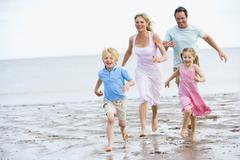 Family running on beach smiling - stock photo