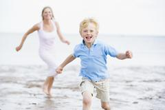 Mother and son running on beach smiling Stock Photos