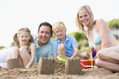Family on beach making sand castles smiling - stock photo