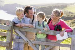 Family on cliffside path leaning on fence and smiling - stock photo