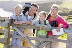 Stock Photo of Family on cliffside path leaning on fence and smiling