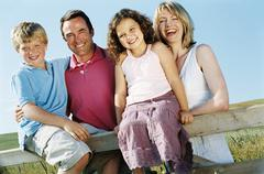 Family on fence outdoors smiling - stock photo