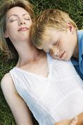 Mother and son lying outdoors sleeping - stock photo