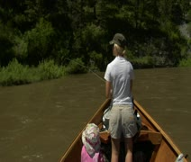 Woman flyfishing from driftboat on river Stock Footage