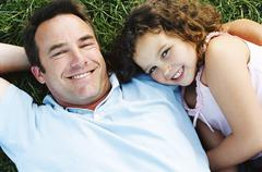 Father and daughter lying outdoors smiling - stock photo