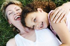 Mother and daughter outdoors smiling - stock photo