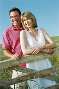 Couple standing outdoors by fence smiling Stock Photos