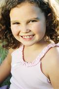 Stock Photo of Young girl sitting outdoors smiling