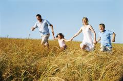 Family running outdoors holding hands smiling - stock photo