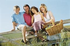Family outdoors by fence with picnic basket smiling - stock photo