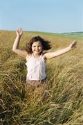 Young girl running outdoors smiling - stock photo