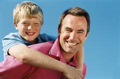 Father giving son piggyback ride outdoors smiling Stock Photos