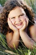 Young girl lying outdoors smiling Stock Photos