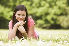 Woman lying outdoors with flower smiling Stock Photos
