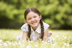 Young girl lying outdoors smiling Stock Photos