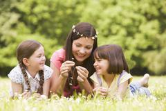 Mother and daughters lying outdoors with flowers smiling - stock photo