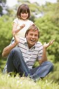 Father and daughter sitting outdoors with flowers smiling - stock photo