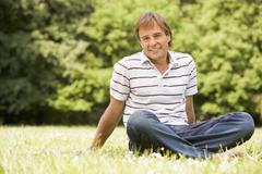 Man sitting outdoors smiling Stock Photos
