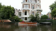 Large home and wooden boat on Amsterdam canal Stock Footage