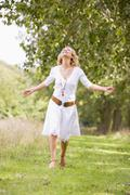 Woman walking on path smiling - stock photo