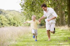 Father and son running on path holding hands smiling - stock photo