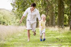 Father and son running on path smiling - stock photo
