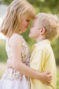 Two young children hugging outdoors Stock Photos
