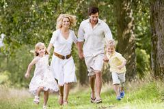 Family running on path holding hands smiling Stock Photos